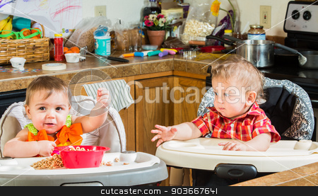 Two Babies Eat Breakfast stock photo, Two babies eating breakfast together in highchairs by Scott Griessel