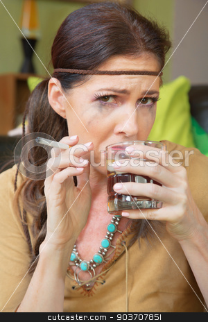 Depressed Woman Drinking Booze stock photo, Lonely and depressed hippie drinking and smoking by Scott Griessel