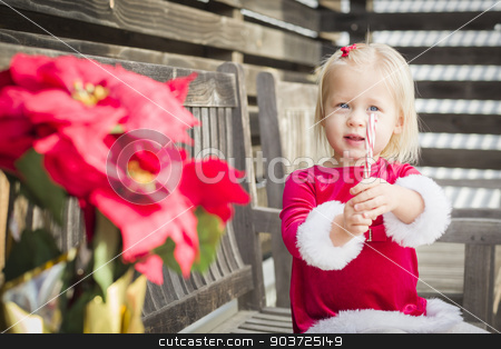 Adorable Little Girl Sitting On Bench with Her Candy Cane stock photo, Adorable Little Girl Sitting On A Bench with Her Candy Cane Outside. by Andy Dean