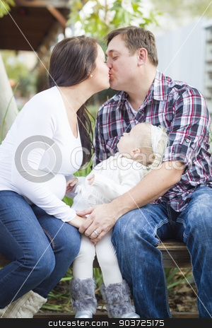 Happy Pregnant Couple Kisses as Baby Girl Watches stock photo, Happy Pregnant Couple Kisses Outside as Baby Girl Watches. by Andy Dean