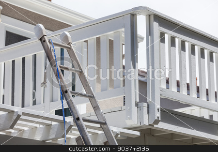 Construction Ladder and Painting Hose Leaning on House Deck stock photo, Construction Ladder and Painting Hose Leaning on White House Deck. by Andy Dean