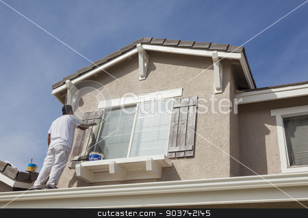 House Painter Painting the Trim And Shutters of Home stock photo, Busy House Painter Painting the Trim And Shutters of A Home. by Andy Dean