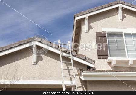Ladder Leaning Up Against A Freshly Painted Home stock photo, Construction Ladder Leaning Up Against A Freshly Painted House. by Andy Dean