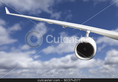 Airplane Wing Against Clouds stock photo, Large Airplane Wing Against Blue Sky and Clouds. by Andy Dean