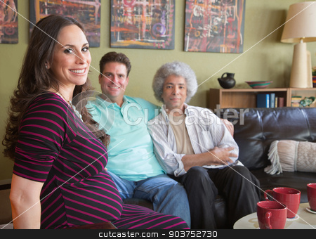 Pregnant Surrogate Mom with Couple stock photo, Happy pregnant surrogate female with mixed gay couple by Scott Griessel