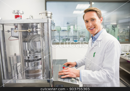 Happy pharmacist pressing button on machine