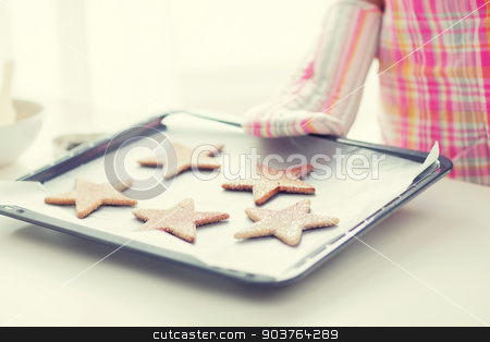 close up of woman with cookies on oven tray