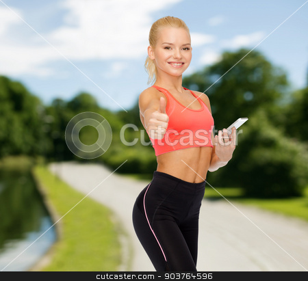 smiling sporty woman with smartphone