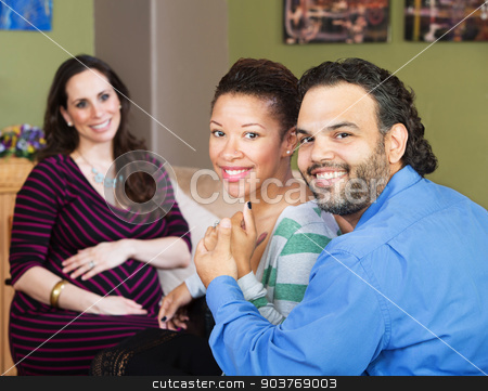 Hispanic Couple with Surrogate Mother stock photo, Smiling Hispanic couple sitting with beautiful surrogate mother by Scott Griessel