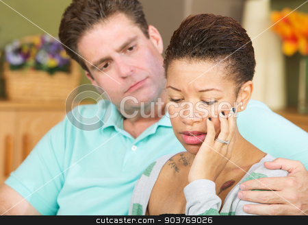 Sad Wife Looking Down stock photo, Anxious beautiful young spouse with concerned husband by Scott Griessel