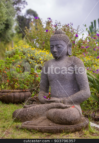 Single Stone Buddha stock photo, Peaceful Stone Garden Buddha Surrounded by Flowers by Scott Griessel