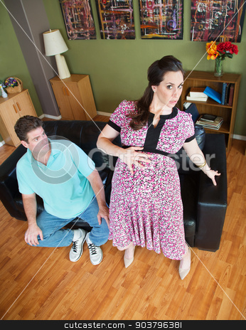Pregnant Wife Getting Up stock photo, Husband watching awkward pregnant wife getting up from sofa by Scott Griessel