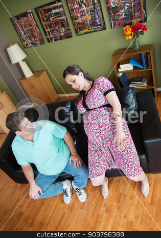 Man Looks at Clumsy Pregnant Woman stock photo, Man looking at clumsy pregnant woman on sofa by Scott Griessel