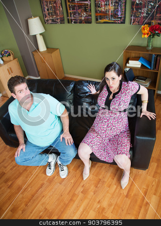 Pregnant Wife Stuck in Sofa stock photo, Man with pregnant woman stuck in sofa by Scott Griessel