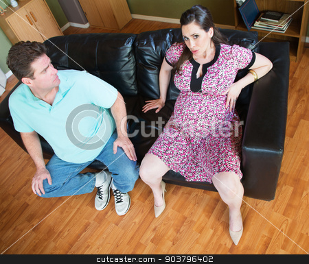 Worried Man with Pregnant Woman stock photo, Pregnant woman sitting on sofa with worried husband by Scott Griessel
