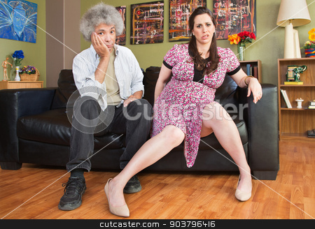 Impatient Pregnant Couple stock photo, Pregnant woman waiting on sofa with impatient husband by Scott Griessel