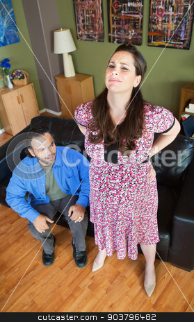 Pregnant Woman with Backache stock photo, Man sitting with pregnant wife suffering from a backache by Scott Griessel