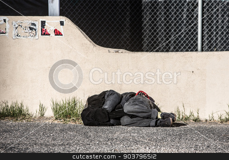 Homeless Person Sleeping stock photo, Homeless person sleeping near wall in parking lot by Scott Griessel