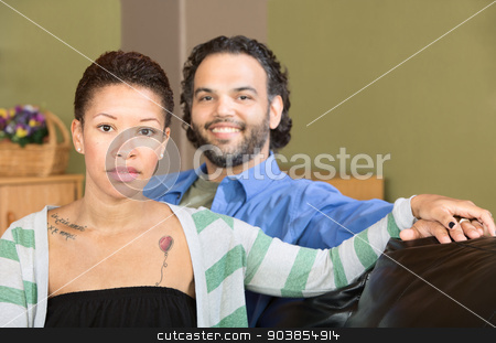 Serious Woman and Smiling Man stock photo, Smiling man sitting with serious Black woman by Scott Griessel