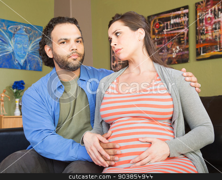 Anxious Pregnant Couple stock photo, Anxious pregnant couple sitting and holding hands by Scott Griessel