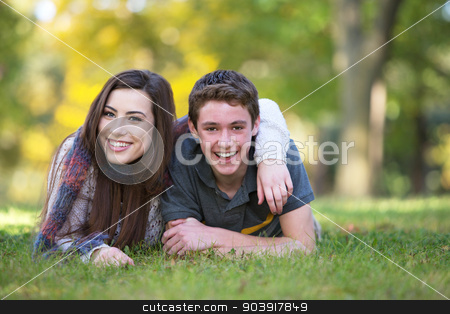 Smiling Boyfriend and Girlfriend stock photo, Smiling male and female teen friends relaxing outdoors by Scott Griessel