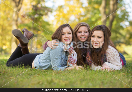 Three Happy Female Friends stock photo, Trio of happy teen girls laying down on grass by Scott Griessel