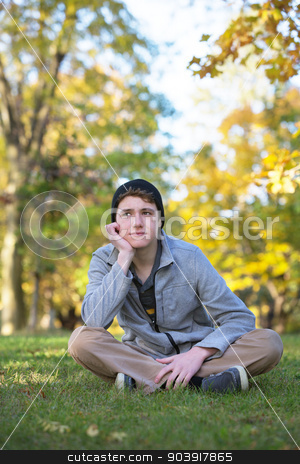 Serious Teen with Hand on Chin stock photo, Serious male teenager sitting and looking over by Scott Griessel