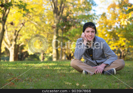 Cute Teen Outdoors Smiling stock photo, Cute teenager sitting on the grass during the fall season by Scott Griessel