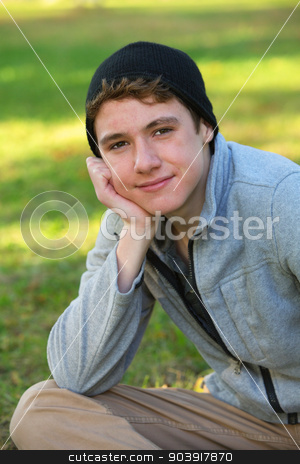 Grinning Teen in Hat stock photo, Grinning male teen with hand on chin sitting outdoors by Scott Griessel