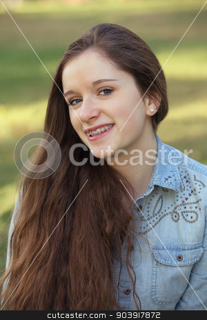 Smiling Teen with Long Hair stock photo, Caucasian teenager with long hair sitting outdoors by Scott Griessel