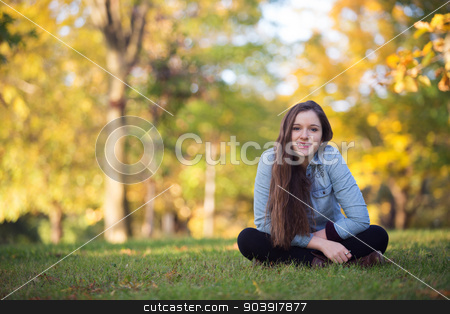 Cheerful Single Teen stock photo, Cheerful single female teenager sitting outdoors on grass by Scott Griessel