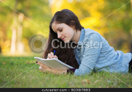 Teen Doing Homework Outside stock photo, Grinning young woman writing on notebook outdoors by Scott Griessel