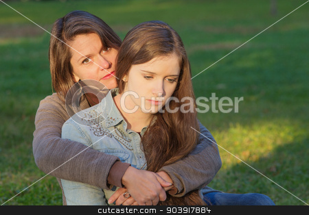 Mother with Sad Daughter stock photo, Concerned European mother holding depressed daughter outdoors by Scott Griessel