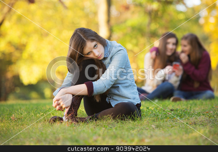 Teens Talking About Girl stock photo, Lonely girl leaning on knee in front of teenagers talking by Scott Griessel
