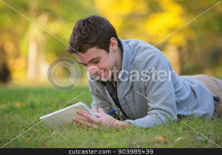 Happy Teen Writing on Grass stock photo, Smiling Caucasian teenager laying down on grass doing homework by Scott Griessel