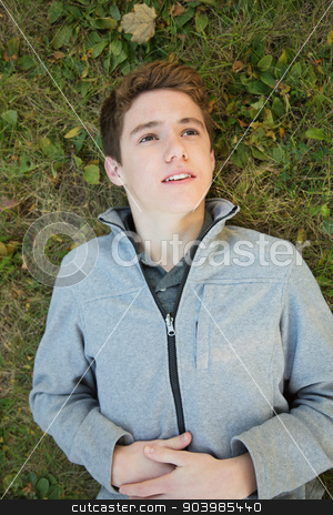 Boy on Ground Looking Up stock photo, Caucasian teenager laying down on grass looking up by Scott Griessel