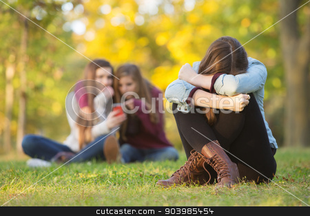 Sad Teen Hiding Face stock photo, Sad teenage woman sitting with head down near laughing group by Scott Griessel