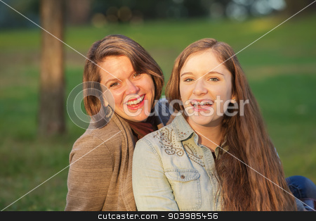 Happy Teen with Mother stock photo, Laughing cute mother and female teenager sitting together by Scott Griessel