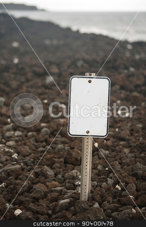 Blank Sign on Rock Beach stock photo, Blank white sign on beach of volcanic rock by Scott Griessel