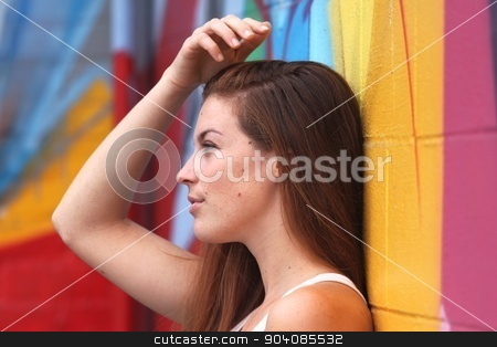 Dream Of A Woman stock photo, Side view portrait of a woman with colorful wall in the background. by Henrik Lehnerer