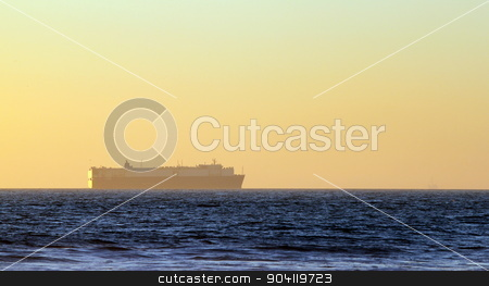 Sunset Ship stock photo, Large container freighter on the horizon during sunset. by Henrik Lehnerer