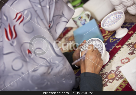 Turkish Woman Illustrating Ceramic Pot stock photo, CAPPADOCIA, TURKEY – APRIL 17: Woman decorates a ceramic bowl with designs typical to the region on April 17, 2012 in Cappadocia, Turkey. by Scott Griessel