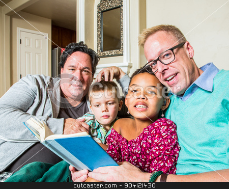 Gay Couple Reads to Children stock photo, An attractive gay couple reads to their children in living room by Scott Griessel