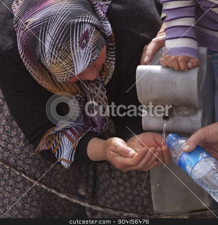 Turkish Woman Collects Water stock photo, Turkish Muslim woman catching water at public fountain by Scott Griessel