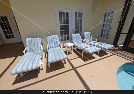 Pool Chairs stock photo, Four pool loungers in a pool area by Lucy Clark