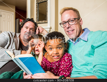 Gay Family Reading Together stock photo, Attractive gay couple reads a book to their children by Scott Griessel