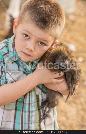 Boy Carrying Chicken stock photo, Caucasian boy outside carrying his pet chicken by Scott Griessel