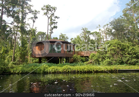 Treehouse stock photo, A treehouse in the forest next to a river by Lucy Clark