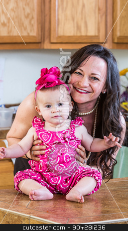 Woman With Cute Baby stock photo, Smiling woman in the kitchen poses with her baby by Scott Griessel