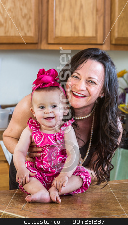 Mother Poses With Her Baby stock photo, Woman in the kitchen poses with her baby by Scott Griessel